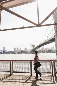USA, New York City, woman walking at East River - UUF09426