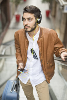 Man with cell phone, headphones and suitcase on escalator - JASF01332