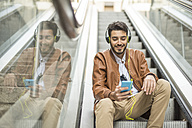 Smiling man with cell phone and headphones sitting on escalator - JASF01335