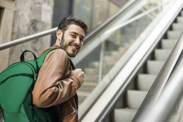 Smiling man with backpack on escalator - JASF01338