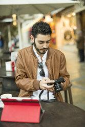 Young man looking at camera at outdoor cafe - JASF01341