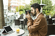 Young man taking pictures at outdoor cafe - JASF01344