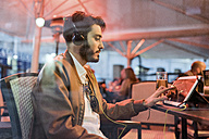 Young man with headphones using tablet at outdoor bar - JASF01347