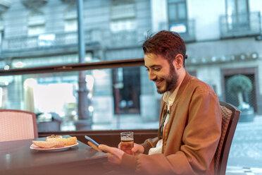 Smiling man looking at cell phone at outdoor bar - JASF01350