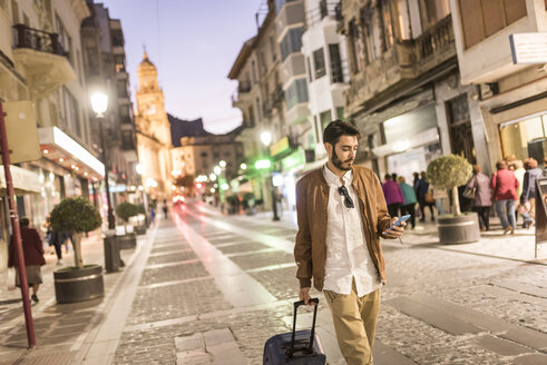 Man with suitcase and cell phone at night in the city - JASF01356