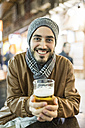 Smiling man with beer at outdoor bar - JASF01359