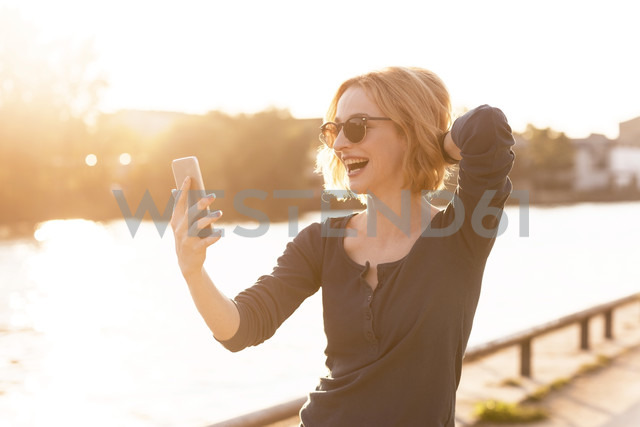 Happy young woman taking selfie with smartphone at backlight - TAMF00862