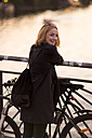 Portrait of smiling young woman with bicycle leaning on railing at evening twilight - TAMF00877