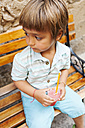 Little boy with cooled soft drink sitting on wooden bench - VABF00845