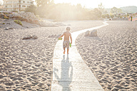 Back view of little boy walking on boardway on the beach at backlight - VABF00848