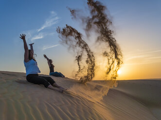 Oman, Al Raka, two young women sitting on a dune in Rimal Al Wahiba desert throwing sand in the air - AMF05101