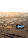 Oman, Al Raka, off-road vehicle parking on dune in Rimal Al Wahiba desert at twilight - AMF05104