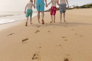 Father and sons walking on the beach - NMSF00002