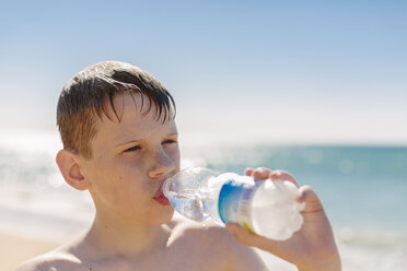 Boy drinking water on the beach - NMSF00008
