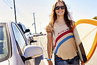 Smiling young woman carrying surfboard on coastal road - WESTF21990
