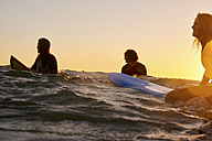 Three surfers in the sea at sunset - WESTF21993