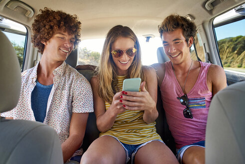 Happy friends checking cell phone in a car - WESTF21999