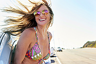 Happy young woman in bikini leaning out of car window - WESTF22005