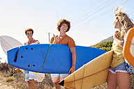 Happy friends carrying surfboards at the coast - WESTF22014