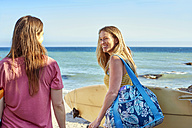 Two happy women carrying surfboards on the beach - WESTF22020