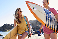 Two happy women carrying surfboards on the beach - WESTF22023