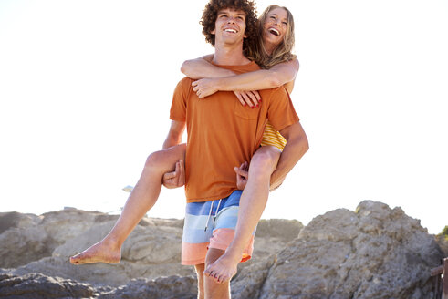 Happy young man carrying girlfriend piggyback on the beach - WESTF22026