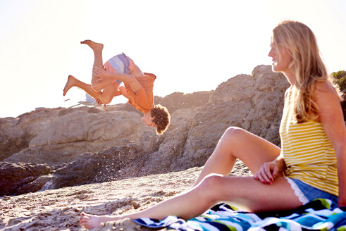Young man with woman on the beach doing a somersault - WESTF22029