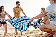 Happy friends spreading out towel on the beach - WESTF22053