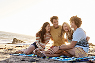 Happy friends sitting on the beach - WESTF22056