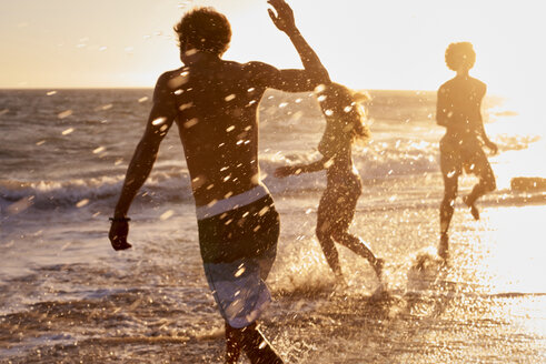 Playful friends on the beach at sunset - WESTF22059