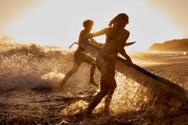 Surfers running into the sea at sunset - WESTF22065