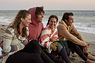 Happy friends sitting on the beach in the evening - WESTF22074