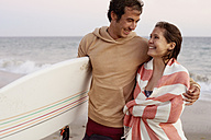 Smiling young couple on the beach carrying surfboard - WESTF22077