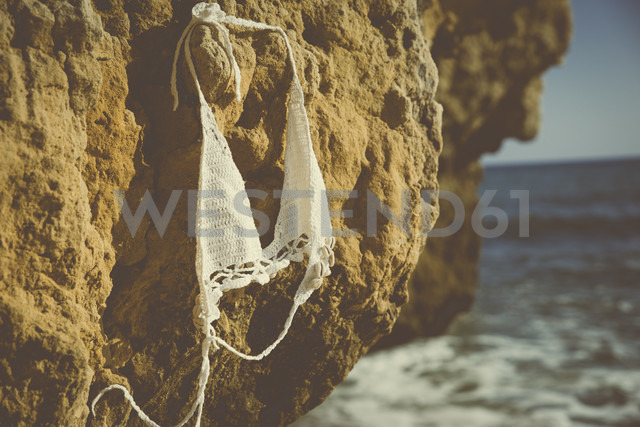 Bikini top hanging on a rock on the beach - CHPF00347