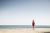 Back view of woman walking on the beach - CHPF00356