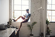 Young man sitting on windowsill looking on cell phone in a loft - WESTF22082