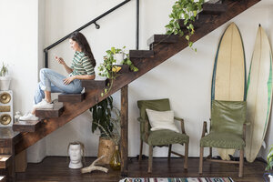 Young woman sitting on stairs in a loft looking at cell phone - WESTF22097