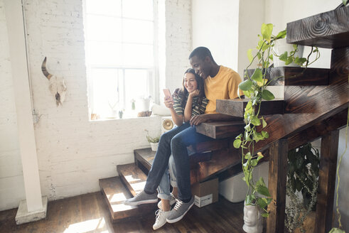 Smiling young couple sitting on stairs in a loft sharing cell phone - WESTF22100