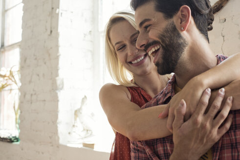 Happy young couple embracing in a loft - WESTF22106