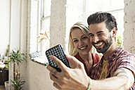 Happy young couple taking a selfie in a loft - WESTF22109
