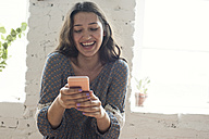 Happy young woman looking on cell phone - WESTF22112