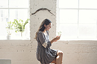 Smiling young woman looking on cell phone in a loft - WESTF22115