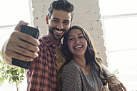 Happy young couple taking a selfie in a loft - WESTF22118