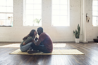 Young couple sitting on carpet in a loft - WESTF22121