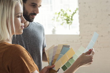 Young couple in a loft looking at color samples - WESTF22124