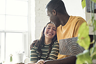 Happy young couple sitting on stairs in a loft - WESTF22127