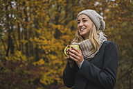 Smiling young woman with hot beverage in autumn forest - KKAF00079