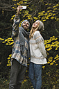 Young couple outdoors in autumn taking a selfie - KKAF00091