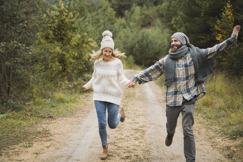 Happy young couple running on path in autumn - KKAF00094