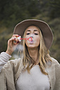 Young woman wearing hat blowing soap bubbles - KKAF00100